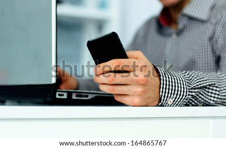 Close-up of male hand holding smartphone and typing on a laptop keyboard - stock photo
