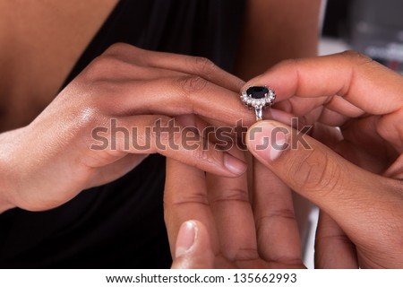 Close Up Of Male Hand Inserting An Engagement Ring Into A Finger - stock photo