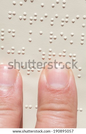 Close up of male hand reading braille text - stock photo
