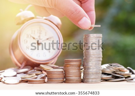 Close up of male hand stacking gold coins with green bokeh background ,Business Finance and Money concept,Save money for prepare in the future. - stock photo