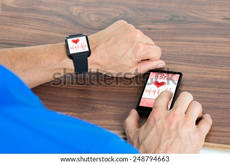 Close-up Of Male Hand With Smartwatch And Cellphone Showing Heartbeat Rate Sitting At The Table - stock photo
