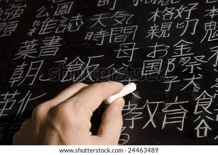 Close up of male hand writing Chinese and Japanese characters on blackboard. The words in Japanese have random meanings. - stock photo