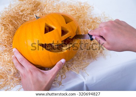 close up of male hands carving pumpkin Jack-O-Lantern for Halloween party - stock photo