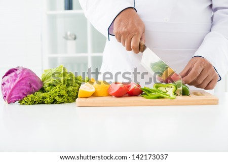 Close-up of male hands cutting vegetables on the board - stock photo