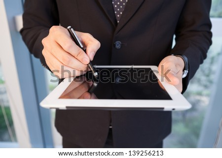 Close-up of male hands holding stylus pen and working on a tablet - stock photo