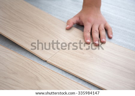 close up of male hands intalling wood flooring - stock photo