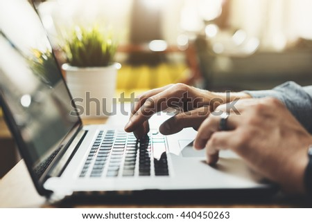 Close-up of male hands using modern laptop at home or cafe interior, young professional businessman working at his office via portable computer, sunshine, film effects - stock photo