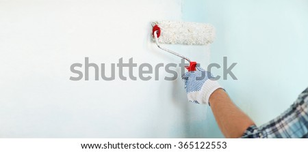 close up of male in gloves painting wall - stock photo