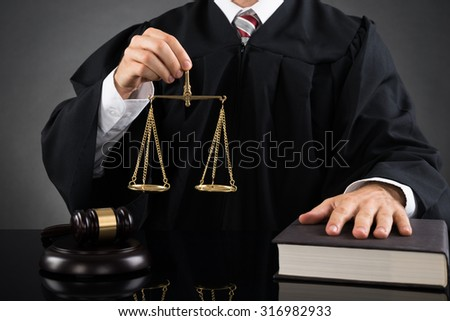 Close-up Of Male Judge Holding Golden Weight Scale At Desk - stock photo