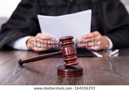 Close-up Of Male Judge In Front Of Mallet Holding Documents - stock photo