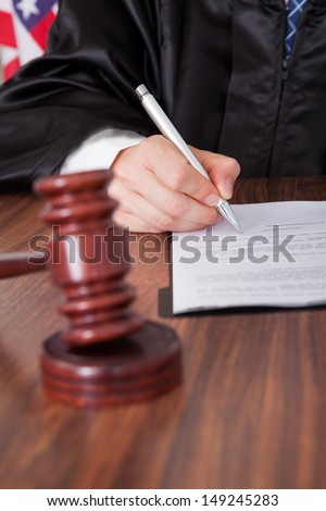 Close-up Of Male Judge  Writing On Paper In Courtroom - stock photo