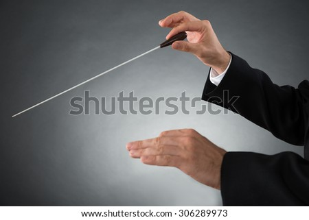 Close-up Of Male Orchestra Conductor Hands Holding Baton - stock photo