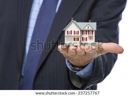 Close Up of Male Real Estate Agent Holding Out A Miniature House in His Hand. - stock photo