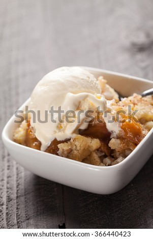 Close up of mall bowl of freshly served peach crisp with scoop of ice cream on top - stock photo