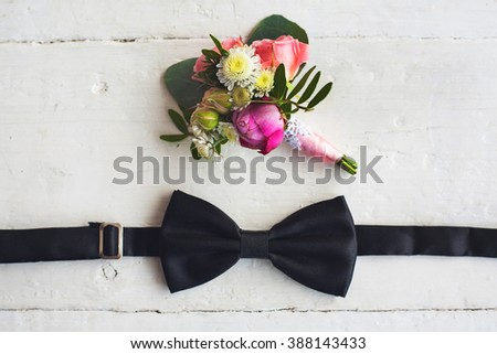 Close up of man accessories. Black bowtie and flower boutonniere on white wood rustic background. Set for formal style of wearing isolated on white wooden background. - stock photo