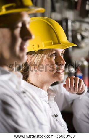 Close up of man and woman wearing hard hats - stock photo
