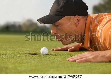 Close-up of man blowing on golf ball - stock photo