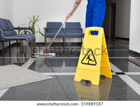 Close-up Of Man Cleaning The Floor With Yellow Wet Floor Sign - stock photo