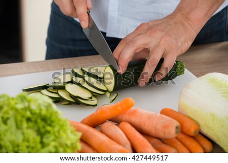 Close-up Of Man Cutting Vegetable On Chopping Board In Kitchen - stock photo