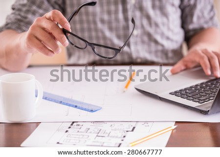 Close-up of man dressed casual using laptop and drinking tea at home office. - stock photo