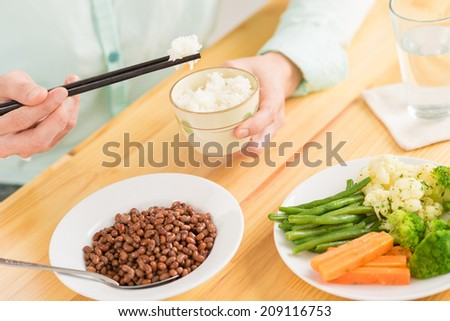 Close-up of man eating rice and vegetables with chopsticks - stock photo