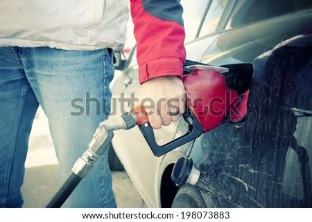 Close up of man filling up the tank of a car - stock photo