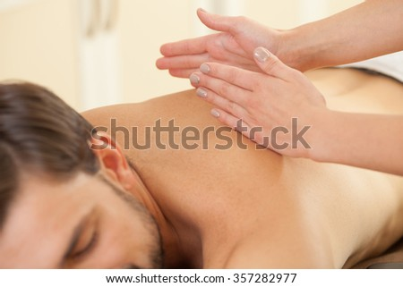 Close up of man getting massage at spa. The female hands of masseuse are massaging his back. The man is lying with relaxation - stock photo