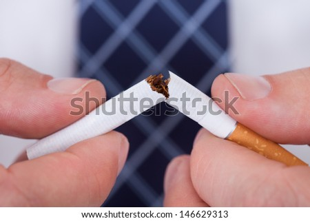 Close-up Of  Man Hand Breaking Cigarette  - stock photo