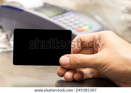 close up of man hand holding blank card with credit card machine in background - stock photo