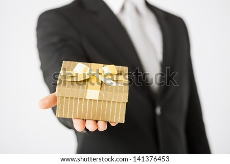 close up of man hands holding gift box. - stock photo