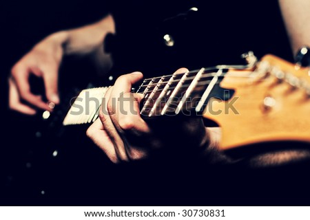close-up of man hands on guitar - stock photo