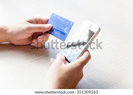 Close-up of man hands with smartphone and credit card as online shopping or online payment concept. Selective and shallow focus. - stock photo