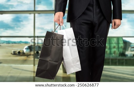 close up of man holding shopping bags walking into airport - stock photo