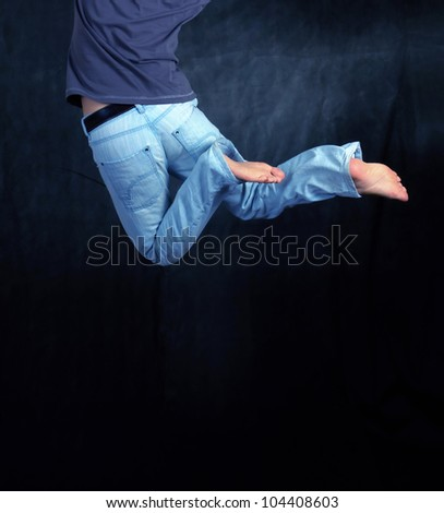 Close up of Man jumping on black background - stock photo