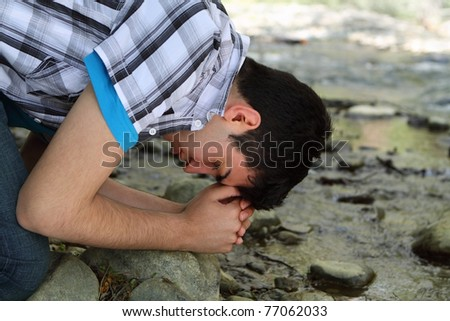 Close-up of man kneeling and praying by a creek - stock photo
