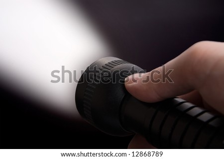 Close up of man's hand holding black  torch, with beam of light visible. - stock photo