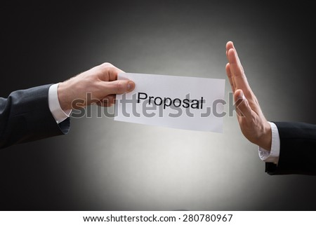Close-up Of Man's Hand Refusing Proposal Sign On Paper - stock photo