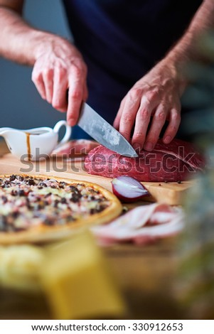 Close-up of man's hands cut beef with knife on board. Sauce-boat, half onion and cooked pizza lying on table too. - stock photo