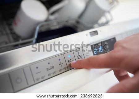 Close Up Of Man Setting Economy Cycle On Dishwasher - stock photo