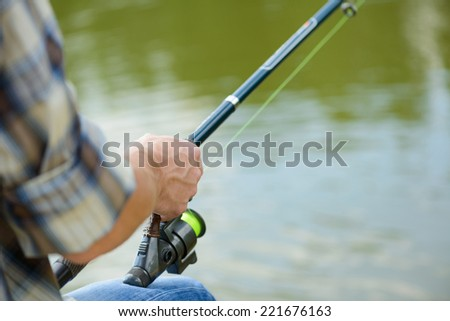 Close up of man sitting on pier with rod - stock photo