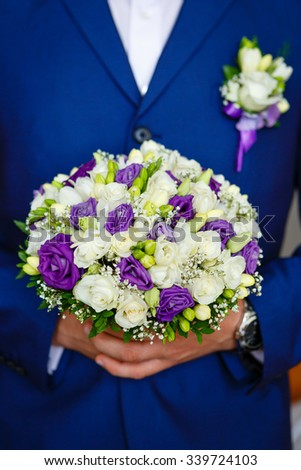 Close-up of Man the groom in the wedding blue suit with bridal bouquet with white and purple roses, flowers boutonniere on his lapel - stock photo