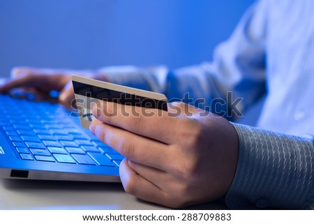 Close up of man using credit card to pay online - stock photo