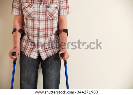 Close Up Of Man Using Crutches - stock photo