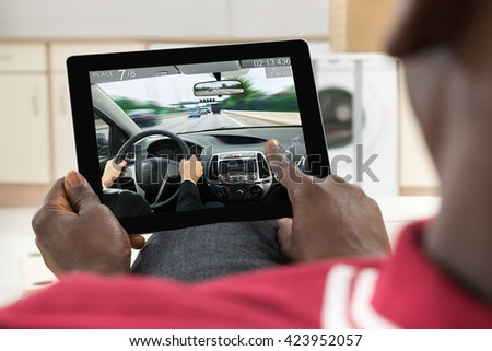 Close-up Of Man Using Digital Tablet Fro Playing Car Game - stock photo