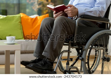 Close-up of man using wheelchair reading book - stock photo