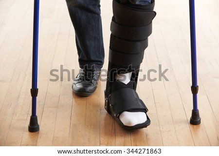 Close Up Of Man Walking With Crutches And Cast - stock photo