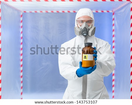 close-up of man wearing protection equipment holding a bottle labeled as deadly substance, in a chamber surounde with red and white tape - stock photo