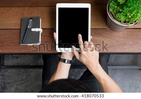 Close up of mans hands using tablet on counter, Image taken from above - stock photo