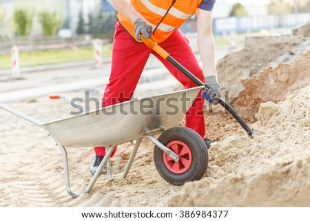 Close up of manual worker with barrow and shovel digging - stock photo