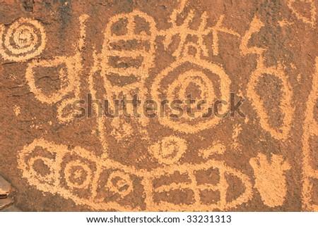 Close up of many petroglyphs carved into rock surface by prehistoric Native American(s). Anasazi Canyon, Southern Utah, USA. - stock photo